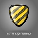 Blank yellow and black caution realistic glossy. Shield with glossy carbon texture and black border isolated on grey background with place for your design and Stock Photography