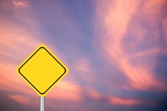 Blank yellow diamond transport sign on purple and pink sky. Background stock photo