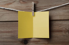 Blank Yellow Greetings Card Pegged to String on Wood. An opened, blank yellow greetings card, pegged on to string against wood plank background royalty free stock photography