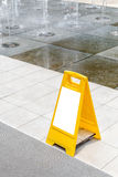 Blank yellow hazard sign alerts for a wet floor in fountain deco Royalty Free Stock Photos