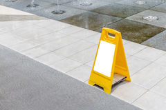 Blank yellow hazard sign alerts for a wet floor in fountain decoration area. royalty free stock photos