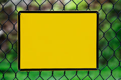 Blank yellow info plate hung on a fence Royalty Free Stock Photo