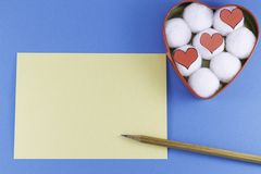 A blank yellow letter with a wooden pencil and a heart-shaped box with cotton balls and hearts inside on a blue background royalty free stock photo