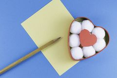 A blank yellow letter with a wooden pencil and a heart-shaped box with cotton balls and red heart inside on a blue background. Letter or invitation Minimalist stock images