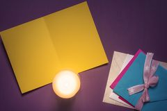Blank yellow message card and candlelight stock photo