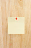Blank yellow note. On wooden background Stock Image