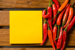 Blank yellow note with chilli on wood background Stock Photo