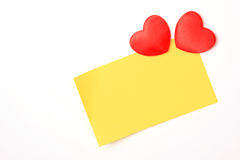 Blank yellow note and hearts. Blank yellow note with copy-space and two hearts on white-board Royalty Free Stock Images