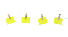 Blank yellow note papers hanging with wood pegs on clothesline. Royalty Free Stock Photography