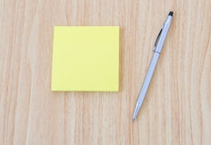 Blank yellow notepad with pen on office wooden table Royalty Free Stock Images