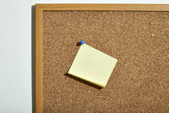 Blank yellow paper note. With blue pin on corkboard royalty free stock photography