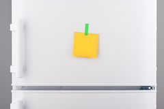 Blank yellow paper note and green sticker on white refrigerator Royalty Free Stock Images