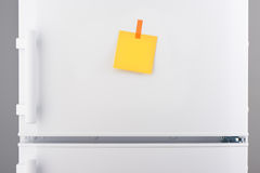 Blank yellow paper note and orange sticker on white refrigerator Stock Photo