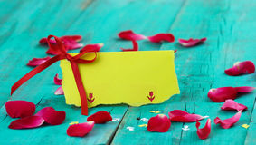 Blank yellow place card with red ribbon and rose petals on antique teal blue distressed wood table Stock Photos