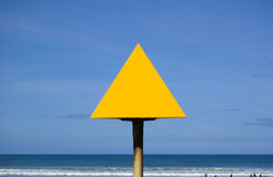 Blank yellow sign at beach. Blank yellow triangle with blue sky background Royalty Free Stock Photography