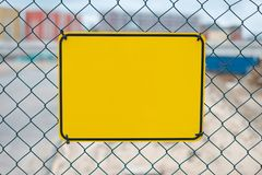 Blank yellow sign on construction site fence - warning sign mockup.  stock photos