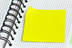 Blank yellow stick note on a spiral notebook from above. Removable self-stick notes. Close-up Stock Images