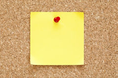 Blank Yellow Sticky Note. Pined on a cork bulletin board Royalty Free Stock Photos