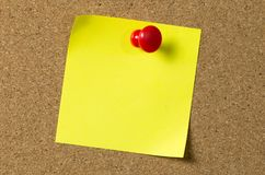 Yellow note pad attached to corkboard. Blank yellow sticky note pad pinned to corkboard using a red thumb tack pin Royalty Free Stock Photos