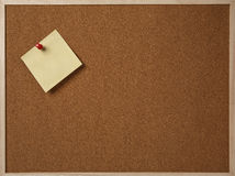 Blank yellow sticky note pinned on a cork bulletin board. Blank yellow sticky note pinned on a cork bulletin board Royalty Free Stock Photo
