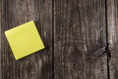Blank Yellow Sticky Note Post It. Stuck on a vintage wood background wall stock photo