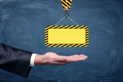 A blank yellow striped construction sign hanging from a crane hook above businessmen`s palm on chalkboard background. Stock Images