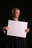 Blank for your text. A young blondie woman holds a blank white sign and whinks at you the viewer blank for your text royalty free stock image