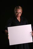 Blank for your text. A young blondie woman holds a blank white sign and whinks at you the viewer blank for your text royalty free stock photo