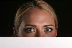 Blank for your text. A young blondie woman holds a blank white sign and whinks at you the viewer blank for your text stock photo
