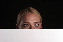 Blank for your text. A young blondie woman holds a blank white sign and whinks at you the viewer blank for your text royalty free stock photography