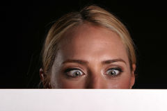 Blank for your text. A young blondie woman holds a blank white sign and whinks at you the viewer blank for your text royalty free stock images