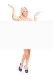 Blanke blonde Frau hinter weißem Panel Lizenzfreie Stockfotos