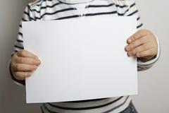 Blankeblad van document in de handen van het kind stock afbeelding