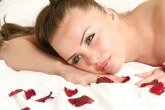 Blankes Mädchen auf Bett mit stieg Stockfoto
