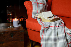 Blanket, books, notepad and pen on armchair with wine, candle an. Soft blanket, book, notepad and pen on elegant armchair, a glass of wine and candle beside it Stock Photography