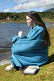 Blanket Clad. Teenager sits besides lake in Mexico.  She is holding a cup of coffee and has her Bible and journal besides her Stock Images