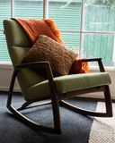 Blanket and cushion on green rocking chair. In front of window stock image