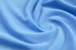 The blanket of furry blue fleece fabric. A background of light blue soft plush fleece material with a lot of relief folds.  stock photos