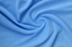 The blanket of furry blue fleece fabric. A background of light blue soft plush fleece material with a lot of relief folds.  royalty free stock image