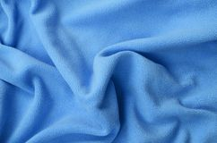 The blanket of furry blue fleece fabric. A background of light blue soft plush fleece material with a lot of relief folds.  stock image