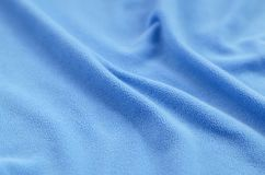 The blanket of furry blue fleece fabric. A background of light blue soft plush fleece material with a lot of relief folds.  royalty free stock images