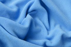 The blanket of furry blue fleece fabric. A background of light blue soft plush fleece material with a lot of relief folds.  stock photo