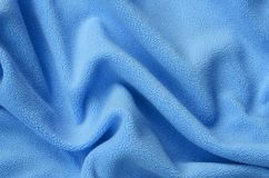The blanket of furry blue fleece fabric. A background of light blue soft plush fleece material with a lot of relief folds.  stock photography