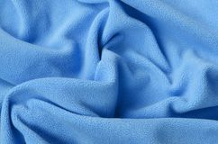 The blanket of furry blue fleece fabric. A background of light blue soft plush fleece material with a lot of relief folds.  royalty free stock photography