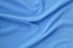 The blanket of furry blue fleece fabric. A background of light blue soft plush fleece material with a lot of relief folds.  stock images
