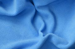 The blanket of furry blue fleece fabric. A background of light blue soft plush fleece material with a lot of relief folds.  royalty free stock photo