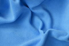 The blanket of furry blue fleece fabric. A background of light blue soft plush fleece material with a lot of relief folds.  royalty free stock photos