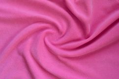 The blanket of furry pink fleece fabric. A background of light pink soft plush fleece material with a lot of relief fold. S stock image
