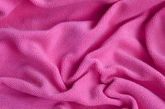 The blanket of furry pink fleece fabric. A background of light pink soft plush fleece material with a lot of relief folds.  Stock Photography
