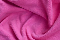 The blanket of furry pink fleece fabric. A background of light pink soft plush fleece material with a lot of relief folds.  royalty free stock photo